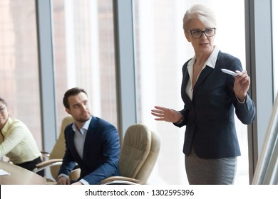 Confident middle aged female leader mentor speaking giving presentation at executive team training, mature business coach presenter speaker explaining new project to board workers at group meeting