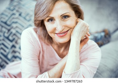 Confident Middle Aged Woman Sitting On Sofa. Relaxing After Yoga. Being In Good Mood. Relaxing Concept.
