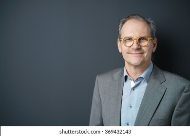 confident middle-aged businessman standing against dark gray background in the studio