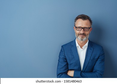 Confident middle-aged man in blue blazer and white shirt, wearing glasses, standing with his arms folded against plain blue background with copy space and looking at camera - Shutterstock ID 1581480463