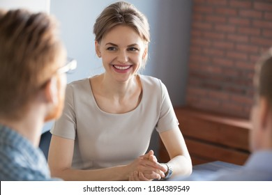 Confident millennial businesswoman smiling looking at male partner at business meeting, happy job applicant being interviewed by hr managers, good performance, recruiting and first impression concept