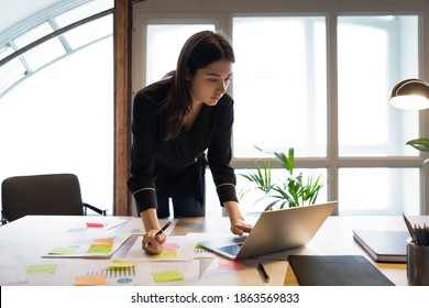 Confident millennial indian female business analyst financial advisor preparing statistic report studying documents on work desk, browsing information online using pc, writing out notes on paper sheet
