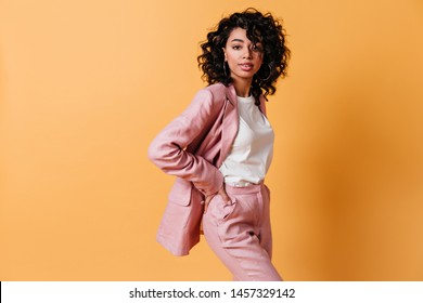 Confident mixed race lady posing on yellow background. Charming girl in formal wear standing with hands on hips.