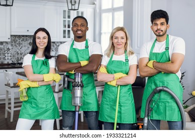 Confident mixed race people standing with crossed arms at apartment with modern interior. Team of cleaning service wearing green apron and yellow rubber gloves.