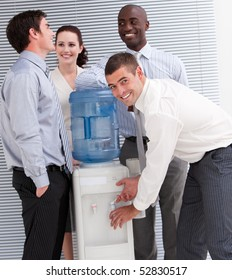 Confident multi-ethnic business people interacting at a watercooler in the office