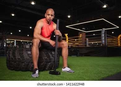 Confident muscular African athlete resting after doing sledgehammer workout at the gym. Handsome male crossfit sportsman relaxing after functional training session with sledgehammer