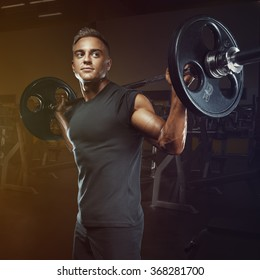 Confident muscular man training squats with barbells over head. Closeup portrait of professional bodybuilder workout with barbell at gym.
