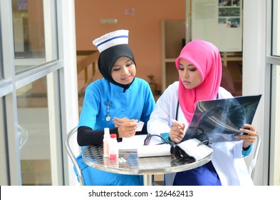 Confident Muslim doctor and nurse busy for medical checking