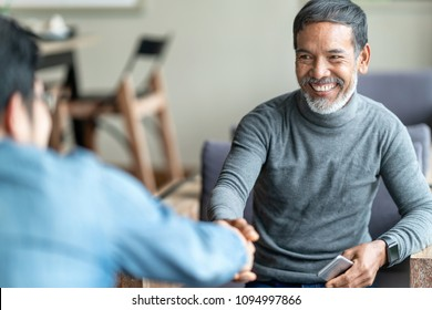Confident muture asian man sitting, smiling and shaking hand with partnership after making profitable agreement. Smart man handshake, deal and greeting concept.