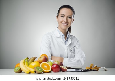 Confident nutritionist working at desk with fresh fruit