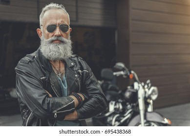 Confident old man having rest near bike