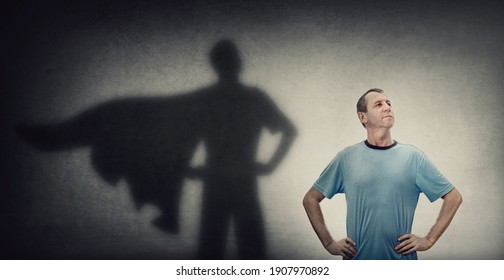 Confident and optimistic middle aged man, hands on hips showing chest, brave gesture, like a powerful superhero casting shadow on the wall. Inner strength, motivation and ambitions, leadership concept