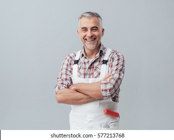 Confident painter and decorator posing with arms crossed and smiling at camera