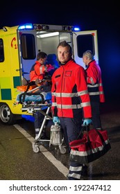 Confident paramedic with team assisting injured patient during road accident