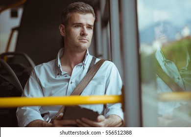 Confident pensive man sitting on the bus, he is looking through a window and using a digital tablet
