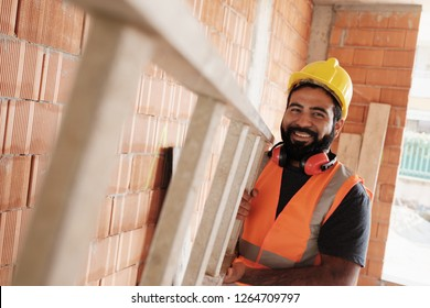 Confident people working in construction site. Portrait of happy hispanic man at work in new housing project. Professional latino worker using ladder and smiling at camera