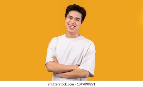 Confident Person. Portrait of smiling asian guy with folded arms looking at camera, wearing white shirt, posing isolated over orange studio background. Happy casual male teenage model laughing - Shutterstock ID 1849899991