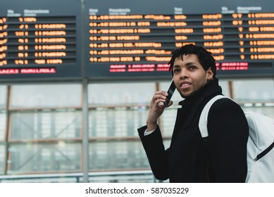 Confident person standing near the display and talking phone in the airport.