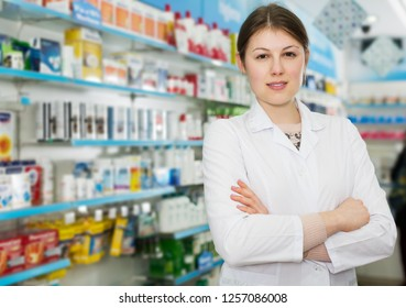 Confident pharmacist standing with arms crossed in interior of pharmacy