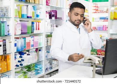 Confident Pharmacist Using Phone While Holding Prescription Pape