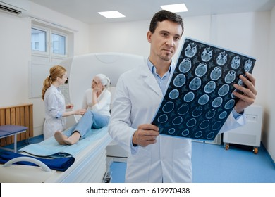 Confident pleasant doctor working with MRI scan results