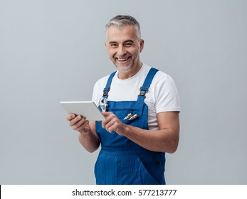Confident plumber or mechanic connecting with a digital tablet and using apps