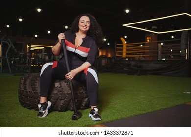 Confident plus size woman smiling to the camera, sitting on a heavy wheel tire at the gym, holding sledgehammer, copy space. Happy overweight sportswoman resting after exercising with sledgehammer