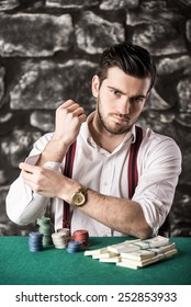 Confident poker player. Serious young man in shirt and suspenders is  sitting at the poker table and looking at the camera.