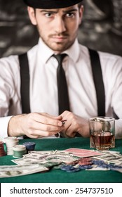 Confident poker player. Serious young man in shirt, hat and suspenders is sitting at the poker table with cards, chips and a glass of whisky.