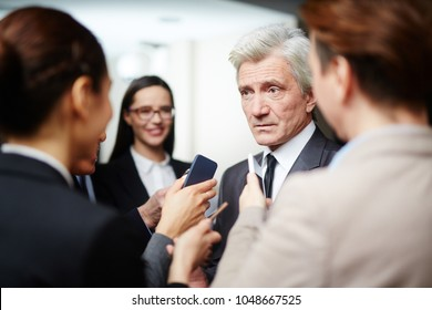 Confident politician in suit asking questions of journalists during press conference