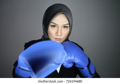 Confident pretty muslim woman executive wearing boxing gloves making hitting posture over dark background. Woman Power Concept. Survival Concept. Girls Power