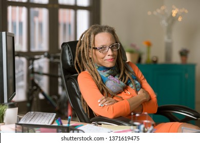 Confident professional with dreadlocks in her office