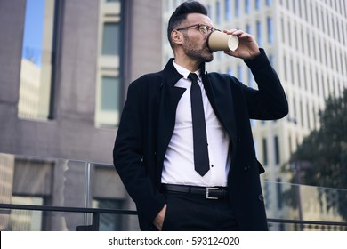 Confident professional handsome project manager of IT company in trendy eyewear drinking coffee outdoors for breakfast in morning standing on urban setting background thinking about plans for day