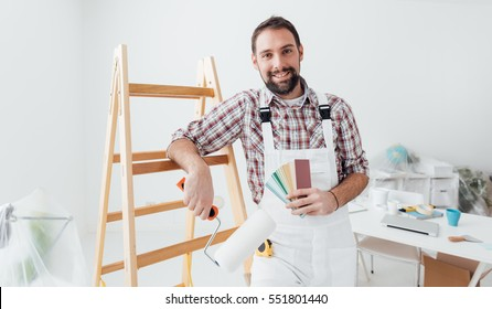 Confident professional painter posing, he is holding a paint roller and color swatches, home renovation and decoration concept