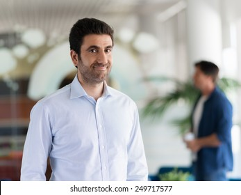 Confident professional standing in an offfice with colllegues on background