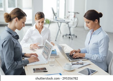 Confident professional women entrepreneurs working at office desk, they are typing on a laptop and using a tablet