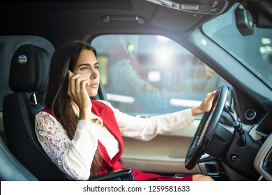Confident prosperous business woman in formal wear having serious mobile phone conversation while driving a luxury car. Proud female owner phoning via cell telephone, sitting in modern automobile
