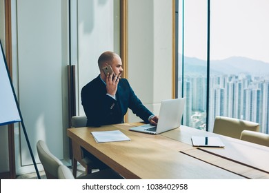 Confident proud ceo in corporate suit calling to manager about accounting reports on smartphone working on developing business project at laptop computer connected to wireless internet in office