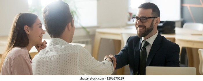 Confident real estate agent financial advisor in suit shaking hands with client respect gratitude gesture, congratulate with property purchase tenancy renting concept, banner for website header design