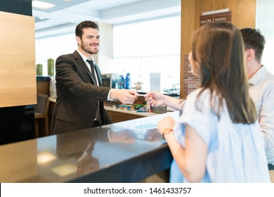 Confident receptionist giving card key to man standing by woman at front desk in lobby