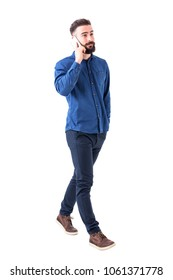 Confident relaxed young adult male business manager walking and talking on the mobile phone. Full body isolated on white background.