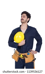 Confident repairman standing hand on waist looking up on the right side with ego face emotion holding his helmet isolated on a white background.