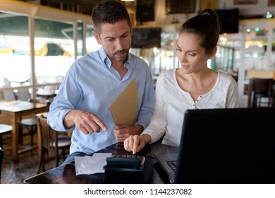confident restaurant manager assisting new employee