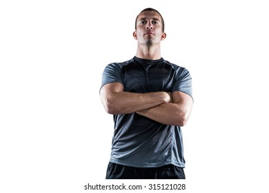 Confident rugby player with arms crossed on white background