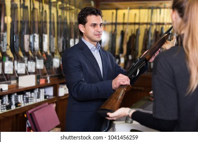 Confident salesman in gun shop showing rifle to female client