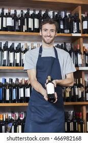 Confident Salesman Showing Wine Bottle