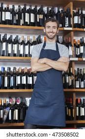 Confident Salesman Standing Arms Crossed In Wine Shop