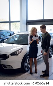 Confident saleswoman showing brochure to customer while standing in car showroom