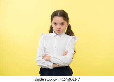 confident schoolgirl. confident and carefree schoolgirl. small schoolgirl with confident look. confident schoolgirl on yellow background