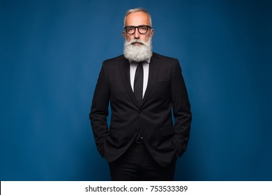 Confident senior bearded man in a suit and tie stand in front of blue isolated background. Fashion posing adult man in fashion glasses and suit